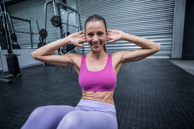 Muskulös kvinna som gör buk- knastrande arkivfoton
