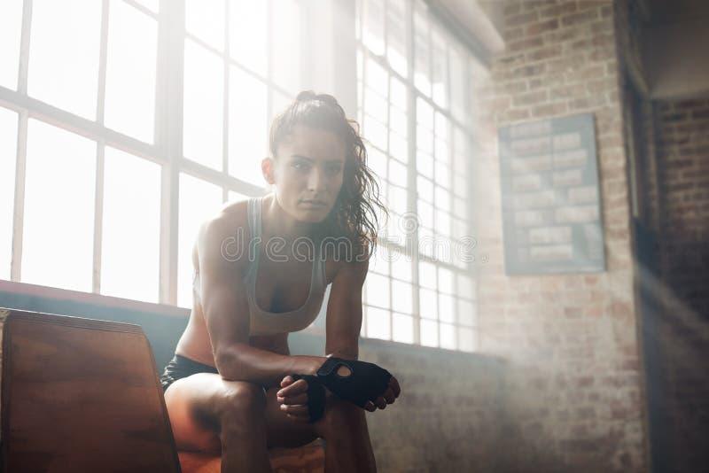 Muskulös kvinna som kopplar av efter genomkörare på idrottshallen royaltyfri foto