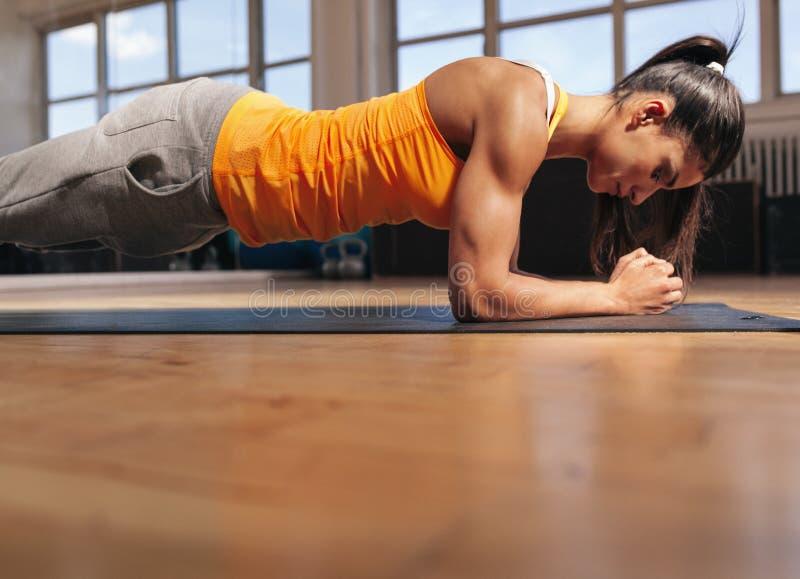 Muskulös kvinnlig som gör kärnagenomkörare i idrottshallen arkivfoton
