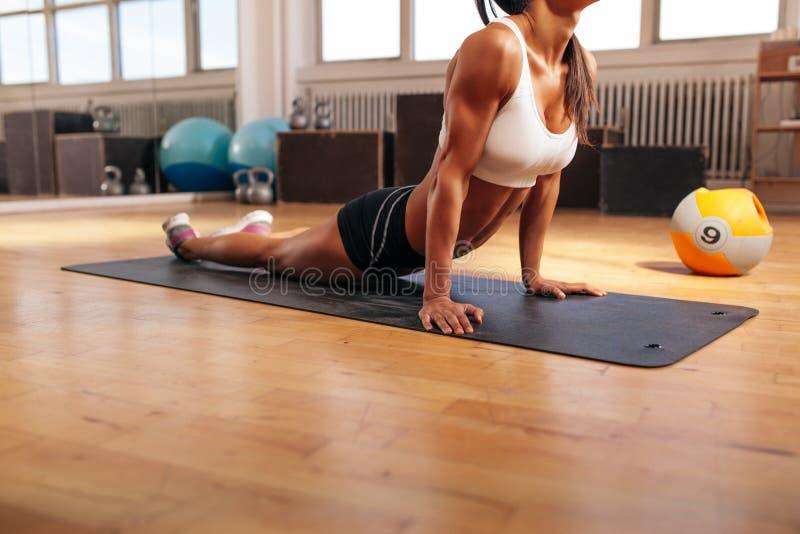 Muskulös kvinnlig som gör sträcka övning i idrottshall royaltyfri bild