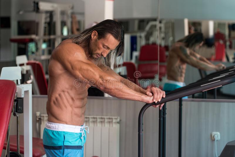 Muskulös man efter övning som vilar i idrottshall royaltyfri foto