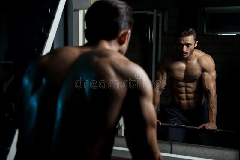 Muskulös man efter övning som vilar i idrottshall royaltyfria bilder