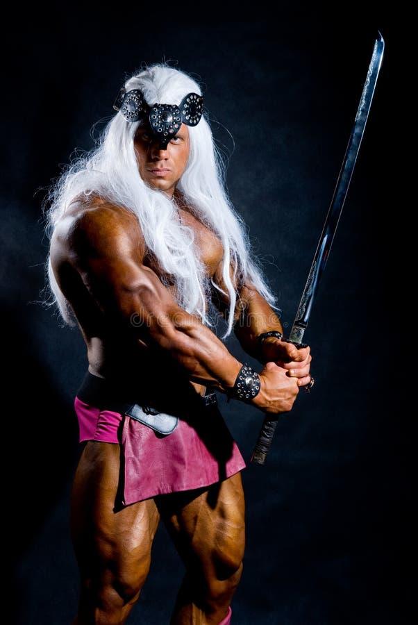 Muskulös man i en avbilda av en barbar med ett lyftt svärd. arkivfoton