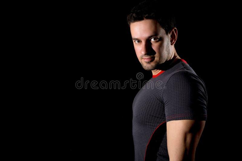 Muskulös man i t-skjortan som isoleras på svart royaltyfri foto