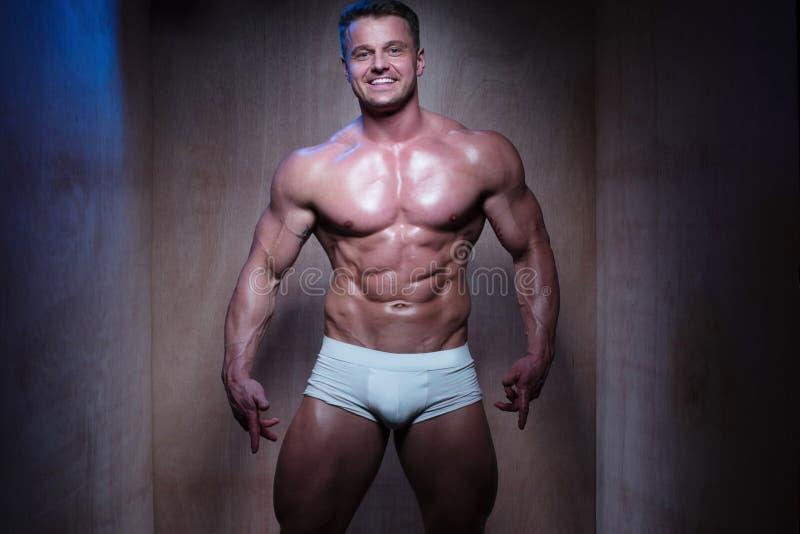 Muskulös man i vita boxarekortslutningar som ner ser arkivfoton