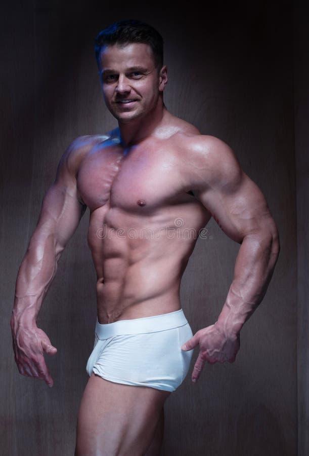 Muskulös man i vita boxarekortslutningar som ner ser royaltyfri fotografi