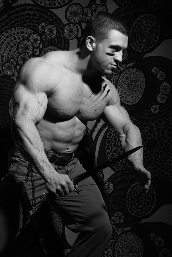 Muskulös man med kniven royaltyfri foto