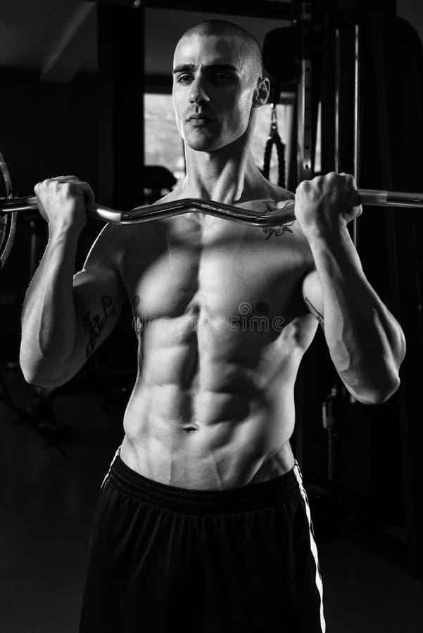Muskulös man som övar biceps med skivstången arkivfoton
