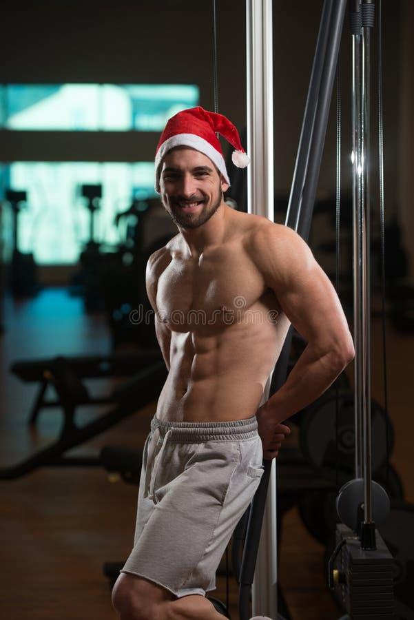 Muskulös man som bär Santa Claus Hat In Gym fotografering för bildbyråer