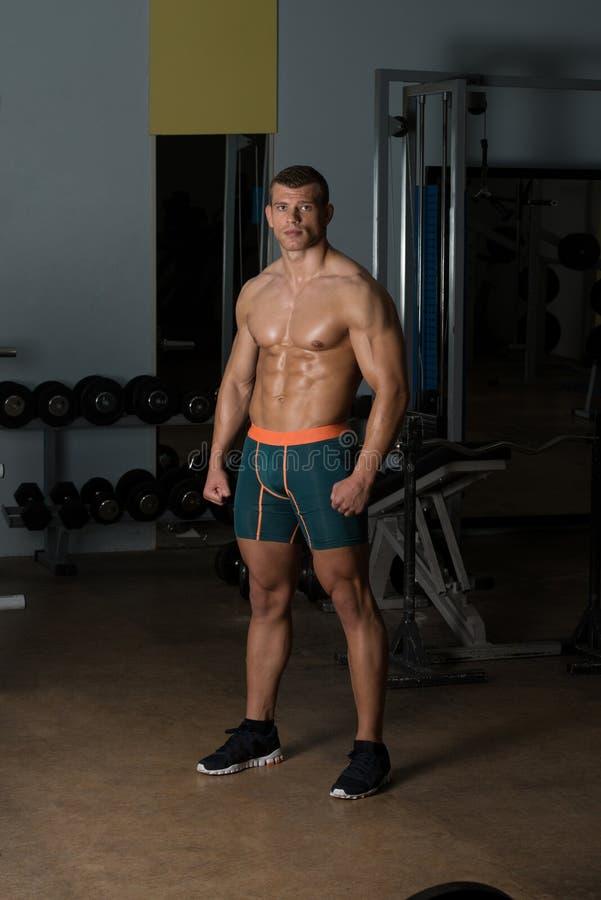 Muskulös man som böjer muskler arkivbild