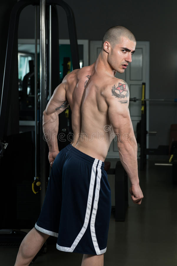 Muskulös man som böjer triceps i idrottshall fotografering för bildbyråer