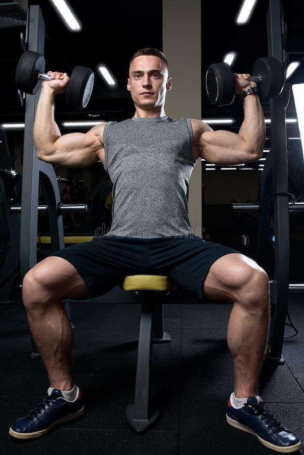 Muskulös man som gör över huvudet press för hantel i idrottshallen fotografering för bildbyråer