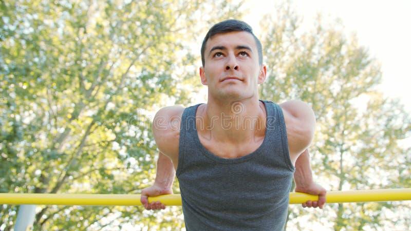 Muskulös man som gör övningar på horisontalstång arkivbild