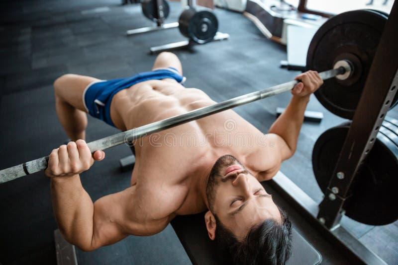 Muskulös man som gör bänkpress fotografering för bildbyråer