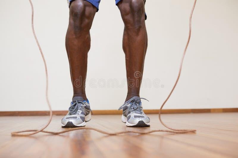 Muskulös man som hoppar over i idrottshall fotografering för bildbyråer