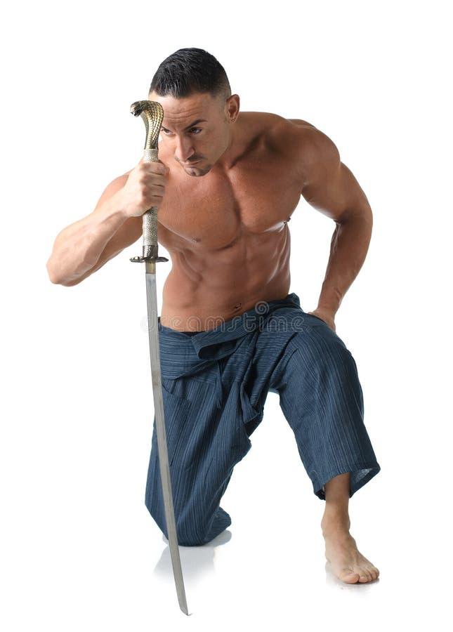 Muskulös man som knäfaller på golvet som är shirtless, med det japanska svärdet arkivbild
