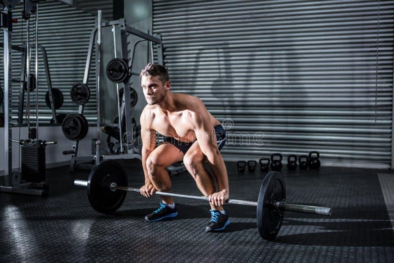 Muskulös man som lyfter en skivstång royaltyfria foton