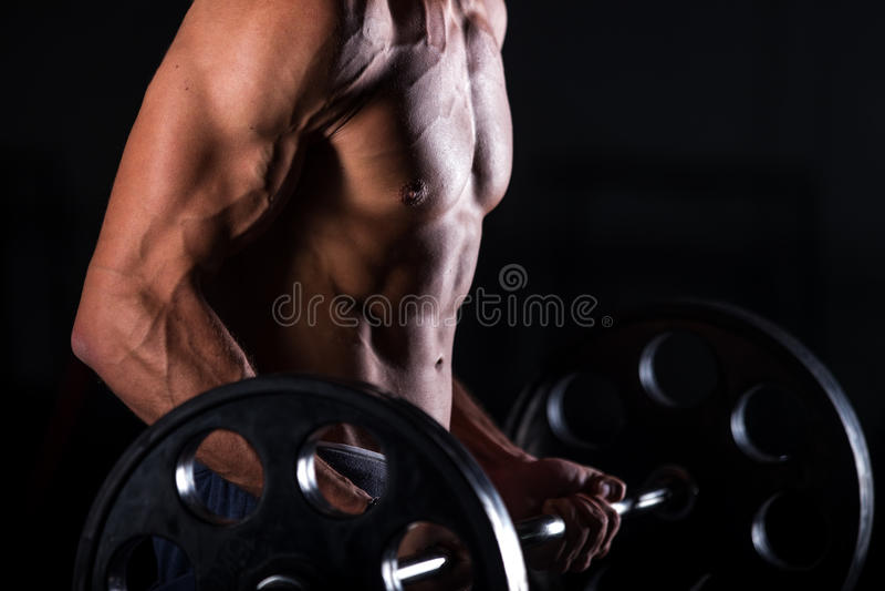 Muskulös man som lyfter en skivstång i konditionmitt arkivfoton
