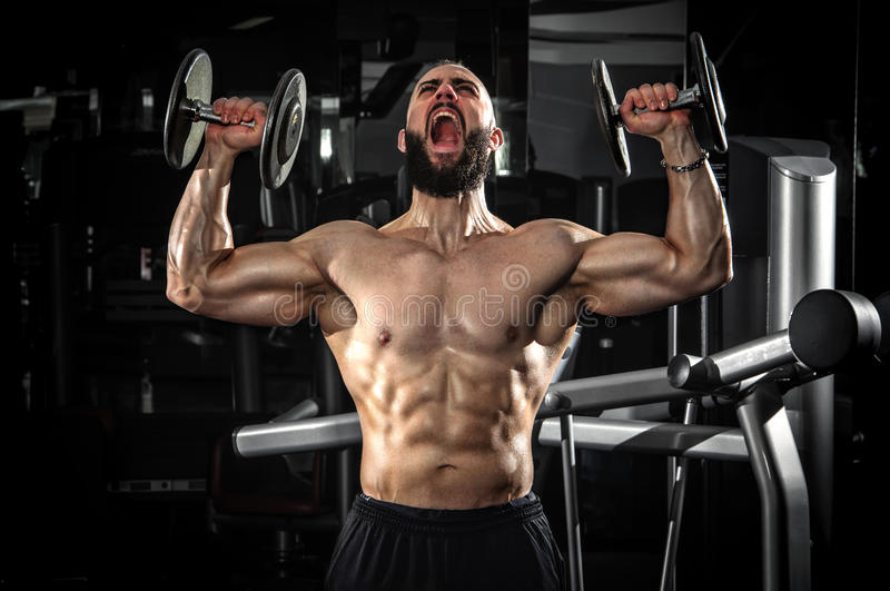 Muskulös man som lyfter några hantlar arkivfoto
