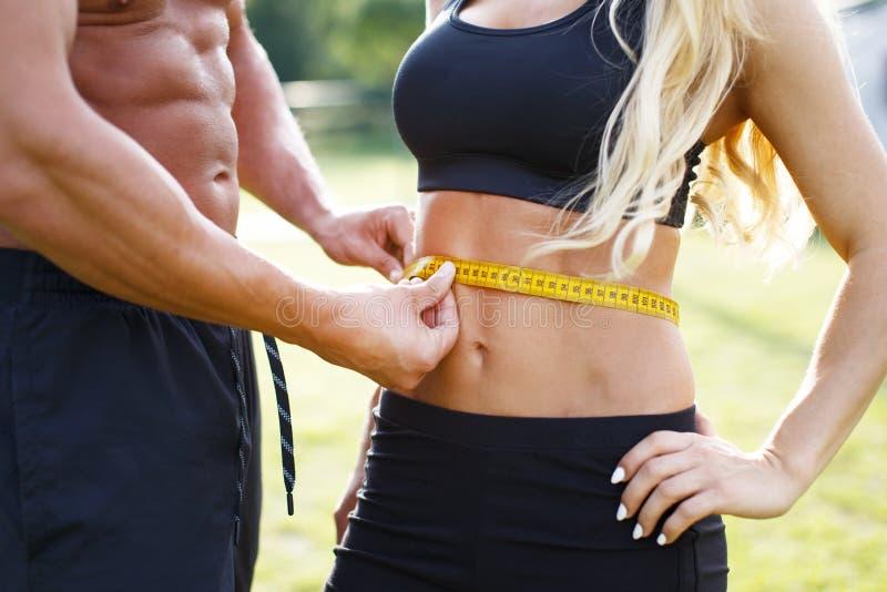 Muskulös man som mäter kvinnaabs med bandet royaltyfri bild