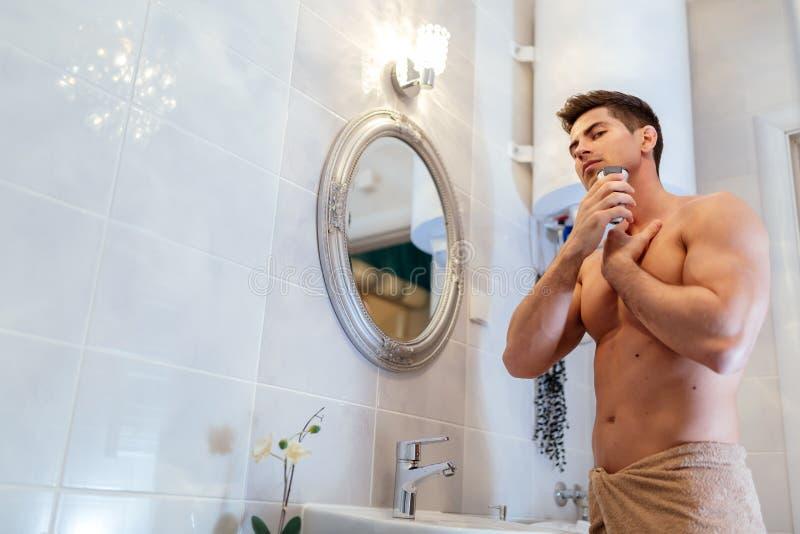 Muskulös man som rakar i badrum arkivbild