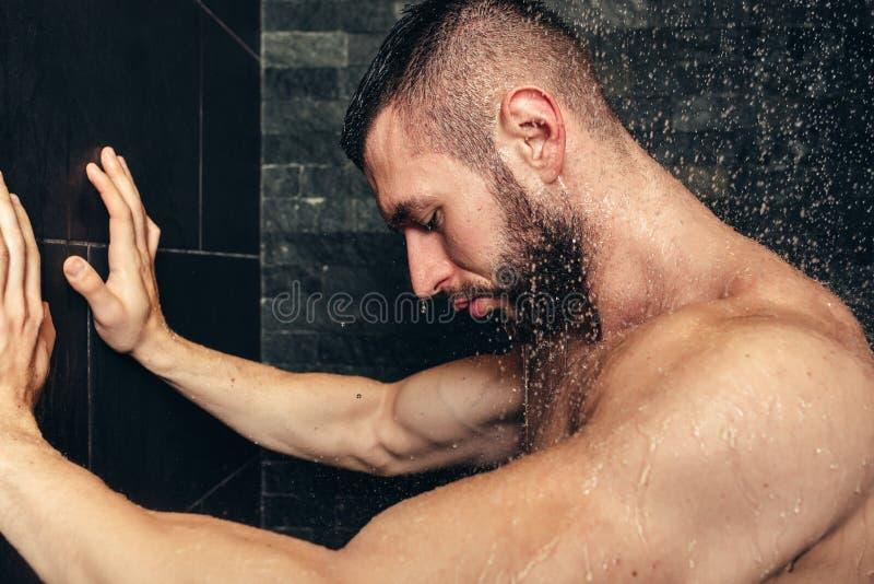 Muskulös man som tar en dusch, detaljer av mannen i rainshower fotografering för bildbyråer