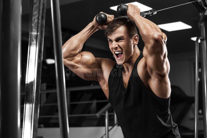 Muskulös man som utarbetar i idrottshall, stark man för kroppsbyggare arkivbild