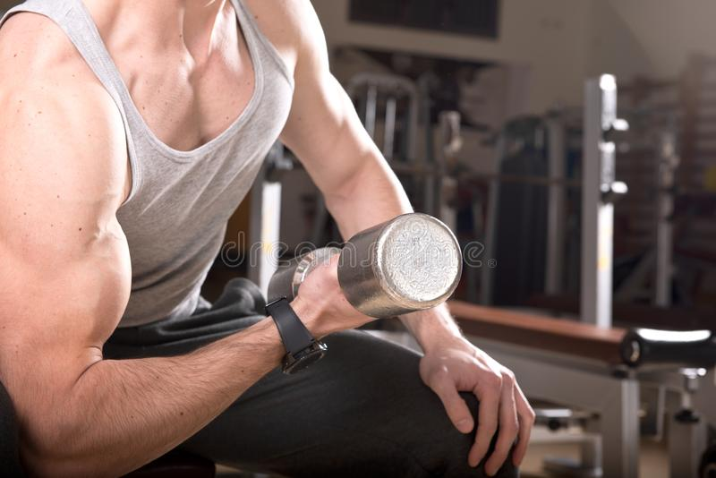 Muskulös man som utarbetar i idrottshallen som gör övningar med hantlar på biceps arkivbild