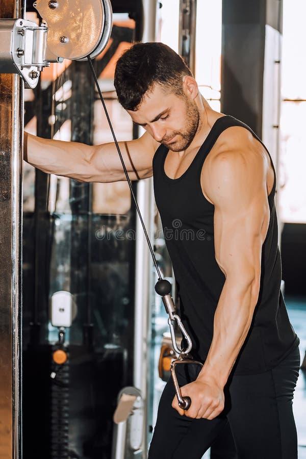 Muskulös man som utarbetar i idrottshallen som gör övningar på triceps arkivbild