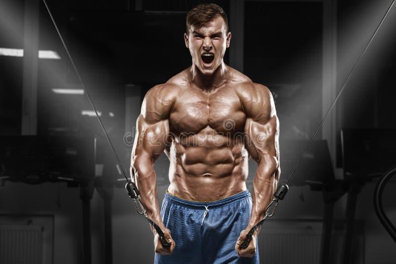 Muskulös man som utarbetar i idrottshallen som gör övningar, stark manlig naken torsoabs arkivbilder