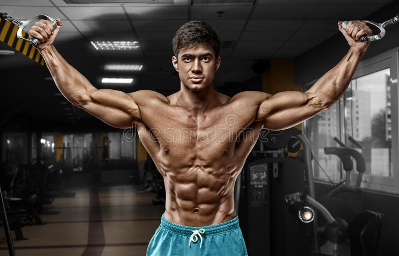 Muskulös man som utarbetar i idrottshallen som gör övningar, stark manlig naken torsoabs royaltyfri fotografi