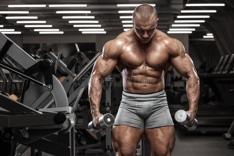Muskulös man som utarbetar i idrottshallen som gör övningar, stark manlig naken torsoabs fotografering för bildbyråer