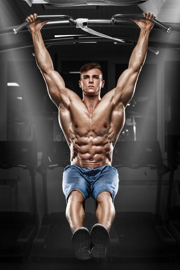 Muskulös man som utarbetar i idrottshallen som gör mageövningar på en horisontalstång, stark manlig naken torsoabs royaltyfria foton