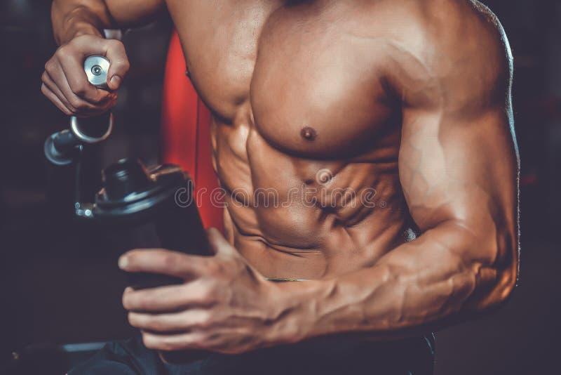 Muskulös man som vilar efter övning och dricker från shaker royaltyfria foton