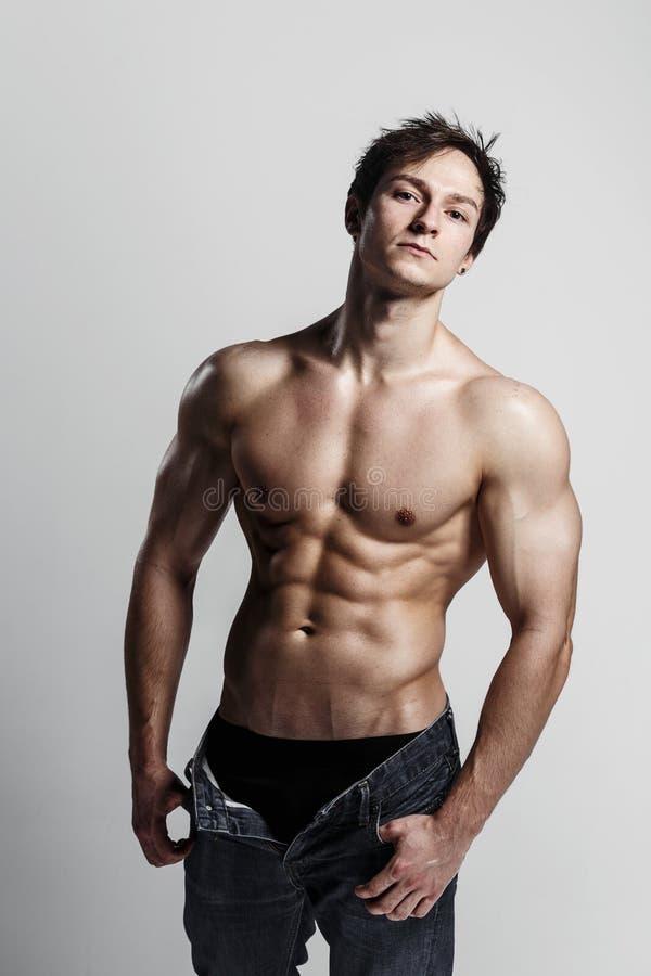 Muskulös manlig modellkroppsbyggare med knäppt upp jeans Sh studio arkivfoton