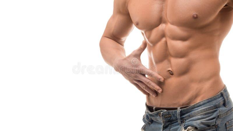 Muskulös manlig torso som isoleras på vit Shirtless man i blåa jaens som trycker på hans abs arkivbilder