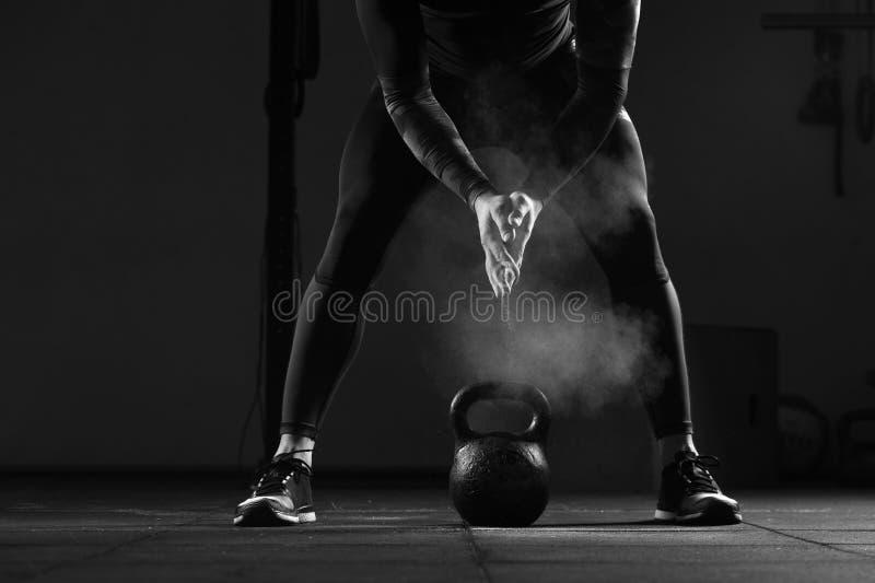 Muskulös manlig vuxen människa som övar med kokkärlklockan arkivbild