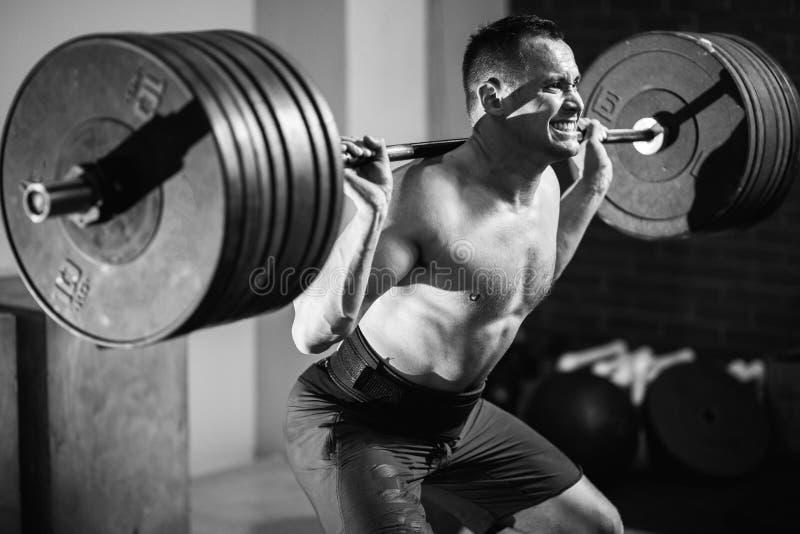 Muskulös manutbildning squats med skivstånger på skuldror royaltyfria foton