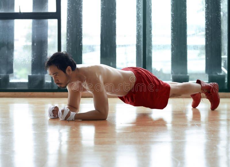 Muskulös och stark asiatisk grabb som gör plankaövning arkivbild