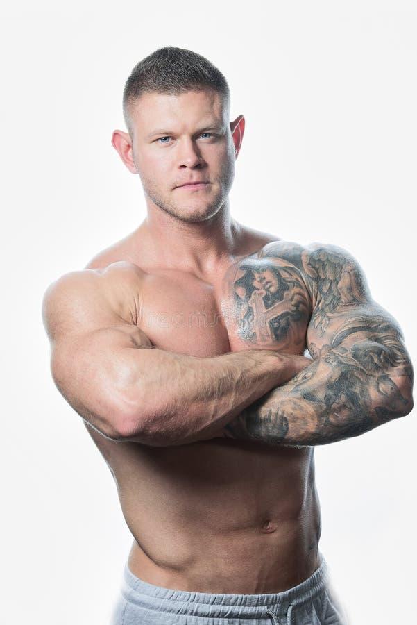 Muskulös shirtless allvarlig man med blåa ögon och tatuering på den vita bakgrunden arkivbilder