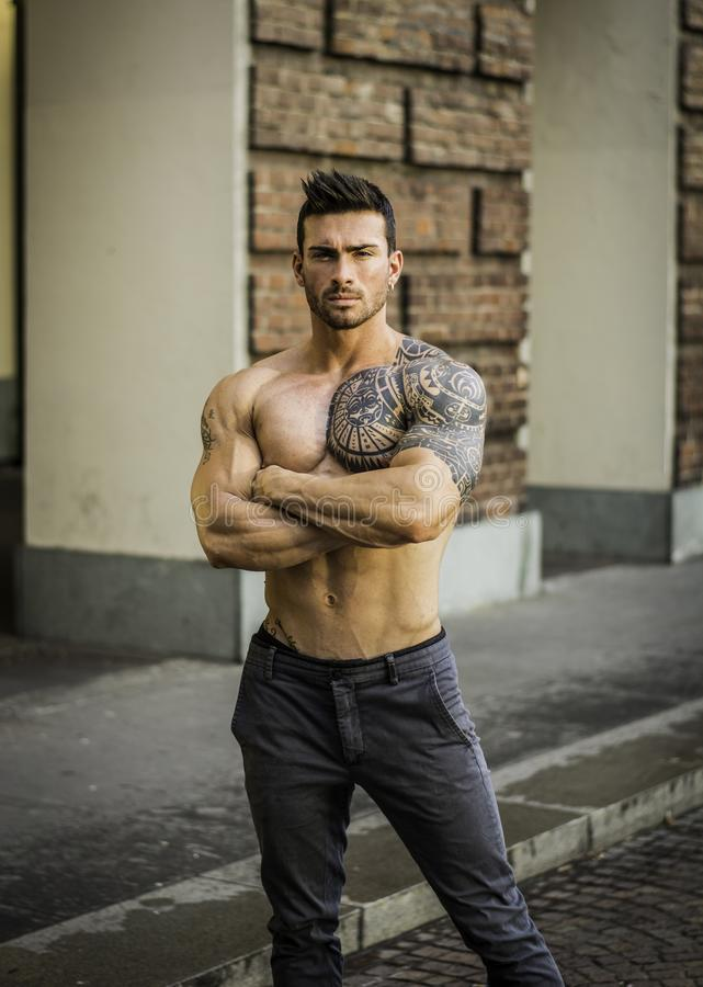 Muskulös shirtless man i stadsmitt royaltyfri foto