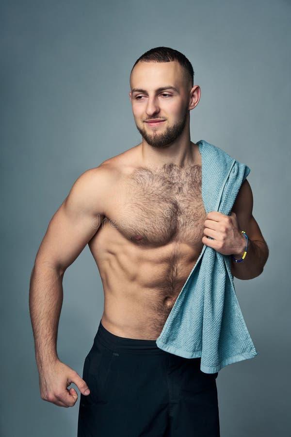 Muskulös shirtless man med handduken över skuldra arkivfoto
