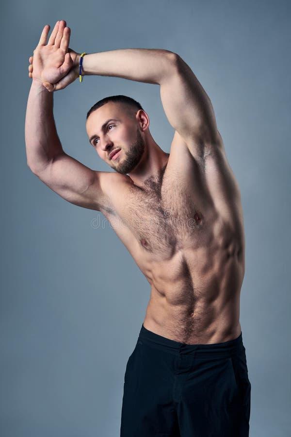 Muskulös shirtless mansträckning royaltyfria foton