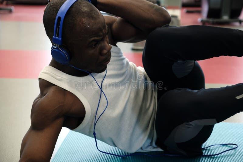 Muskulös svart man som vaggar press som ligger på hans sida arkivbilder