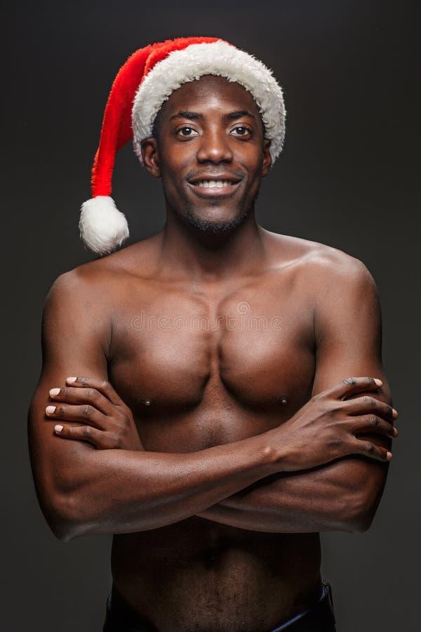 Muskulös svart shirtless ung man i den Santa Claus hatten arkivbilder