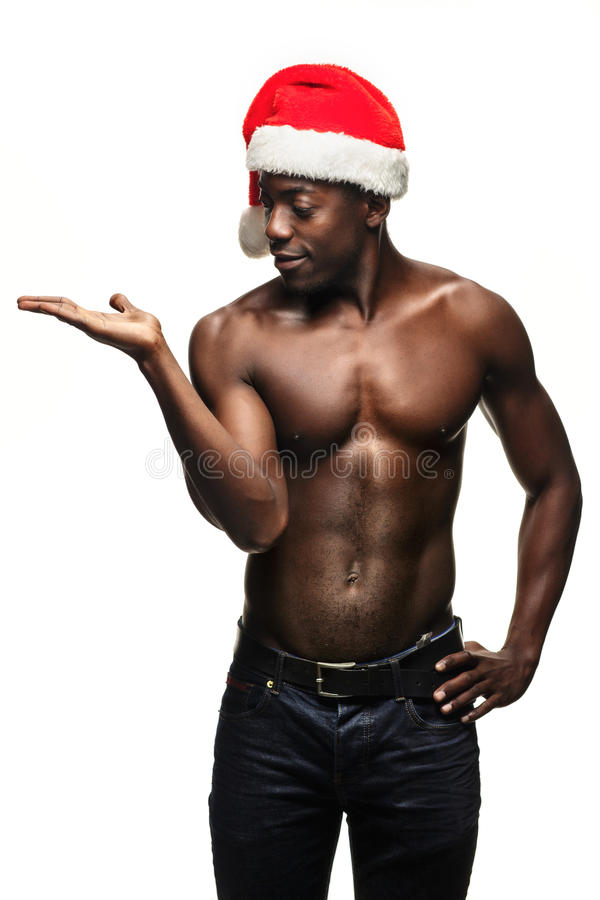 Muskulös svart shirtless ung man i den Santa Claus hatten arkivfoto
