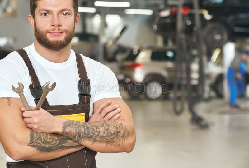 Muskulös tattoed repairman som poserar i autoservice arkivfoton