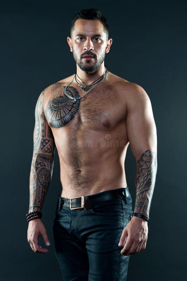 Muskulös tatuerad attraktiv idrottsman nenblick Sport- och modebegrepp Stilig färdig man som poserar att bära i jeans med fotografering för bildbyråer