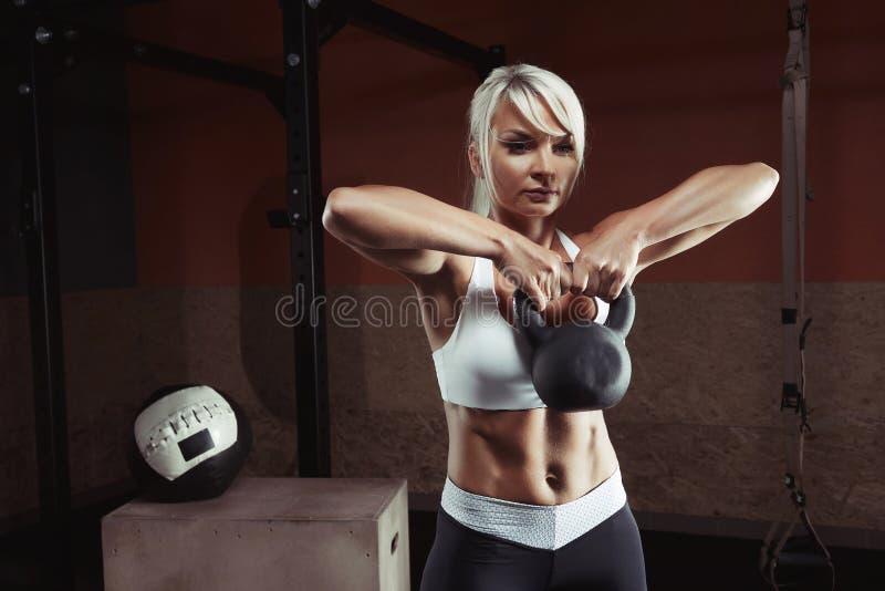 Muskulös ung konditionkvinna som lyfter en vikt i idrottshallen arkivfoto