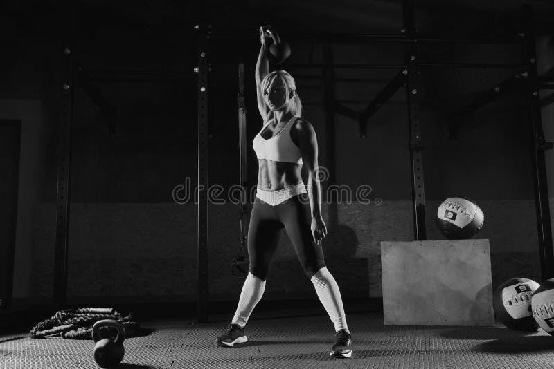 Muskulös ung konditionkvinna som lyfter en vikt i idrottshallen royaltyfria bilder